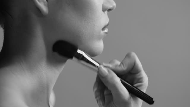 メイクアップアーティストが彼女の顔と首にブロンザーを適用する女の子のクローズアップサイドビュー。白黒ビデオ。 - メイクアップブラシ点の映像素材/bロール