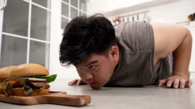 close-up side view: thai overweight man doing push ups in order to eat hamburger - overweight yoga stock videos & royalty-free footage