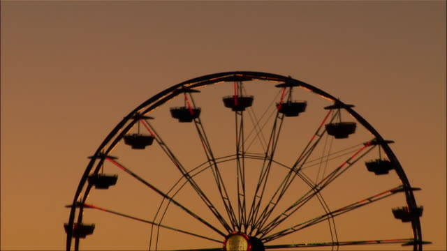 close-up. silhouette of illuminated ferris wheel at santa monica pier. - ferris wheel stock videos & royalty-free footage