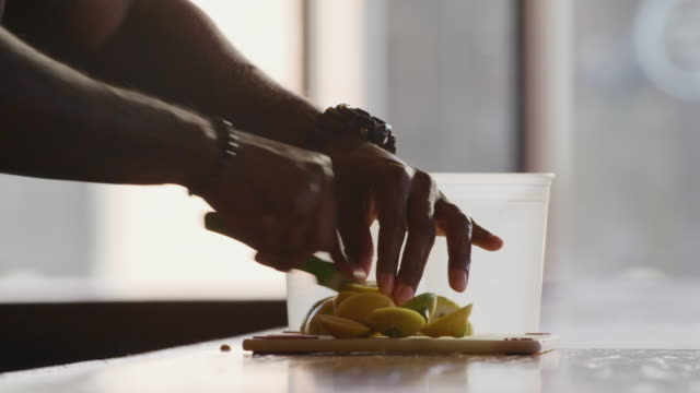 closeup silhouetted bartender's hands slicing lemons in preparation of his shift. - lemon fruit stock videos & royalty-free footage