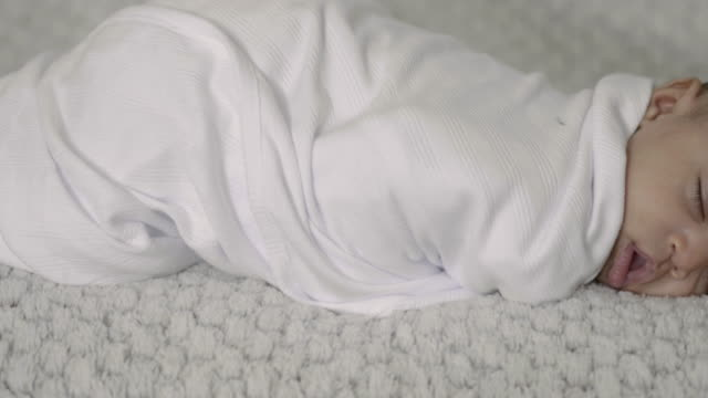 Close-Up Sliding Shot of A Baby Wrapped in a Blanket While Napping