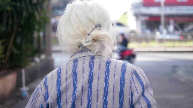 Primer plano: lenta una señora mayor asiático camina ejercicio en manos de la mañana en bastón.