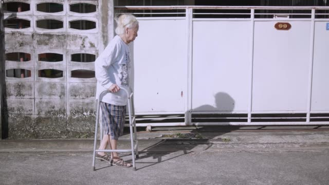 close-up : slow motion asian older lady walks exercise in morning hands on walking stick in the morning. sitting to take a rest. easy walk. - walking frame stock videos & royalty-free footage