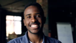 Close-up slow motion portrait of handsome African American man standing in loft style office, looking at camera and smiling. People, work and happiness concept.
