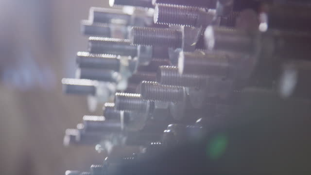 close-up slow motion shot a person wearing protective work gloves screwing nuts on to a wall of bolts (manufacturing) - bolt stock videos & royalty-free footage