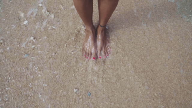vídeos de stock, filmes e b-roll de close-up slow motion shot of female feet standing on a sandy beach with waves splashing up and washing the sand away - surfe