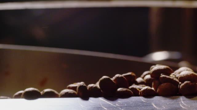 vídeos y material grabado en eventos de stock de primer plano a cámara lenta de frijoles de café tostador girando alrededor de una bandeja de enfriamiento de tostador de café comercial grande - preparación de alimentos
