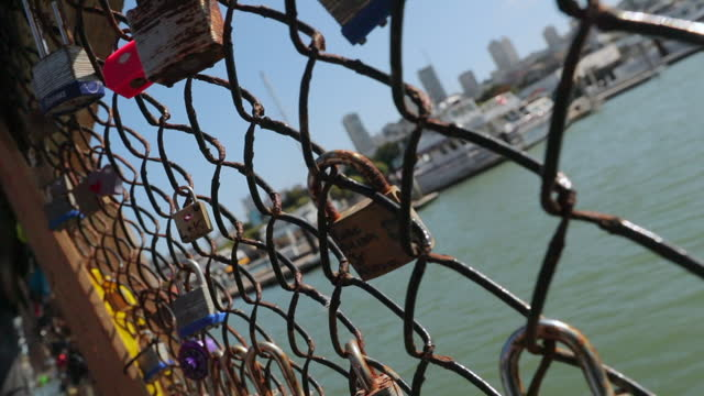 vidéos et rushes de close-up slow motion shot of rusty padlocks hanging bridge railing - san francisco, california - chain bridge suspension bridge