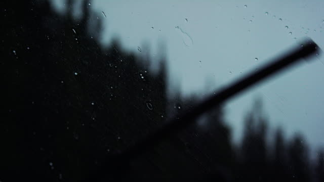 vidéos et rushes de plan rapproché slow motion shot of windshield wipers cleaning rain off of a vehicle's windshield while driving near a forest under an overcast sky at twilight - aube