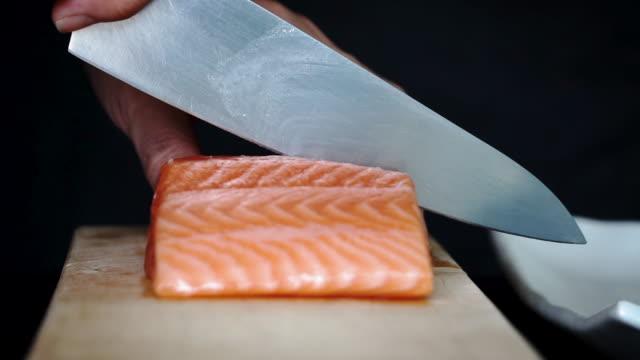 vídeos de stock e filmes b-roll de close-up slow-motion of using knife cut fresh salmon on wooden chopping board - filete de salmão