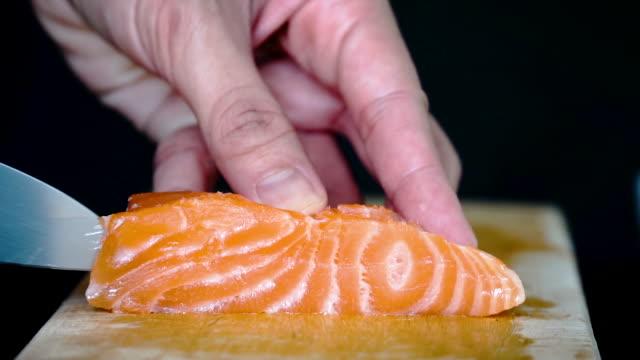 vídeos de stock e filmes b-roll de close-up slow-motion of using knife slice fresh salmon on wooden chopping board - filete de salmão