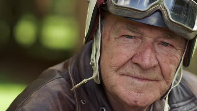 close-up smiling senior man wearing motorcycle helmet and motorcycle goggles / washington, usa - バイカー点の映像素材/bロール