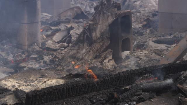 vidéos et rushes de close-up smoldering rubble of a burned structure - parpaing