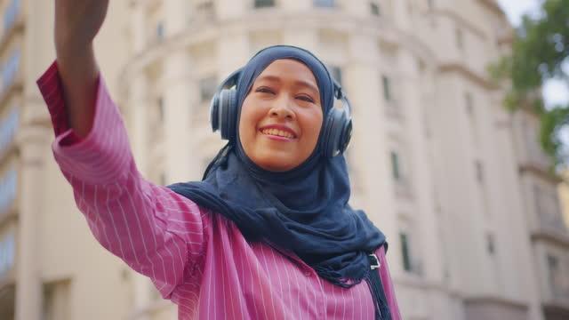 när-up : sydostasiatiska muslimska kvinna bär hijab och trådlösa hörlurar lyssna podcast eller musik och ta en selfie på mobiltelefon när du reser staden på morgonen. - east asian ethnicity bildbanksvideor och videomaterial från bakom kulisserna