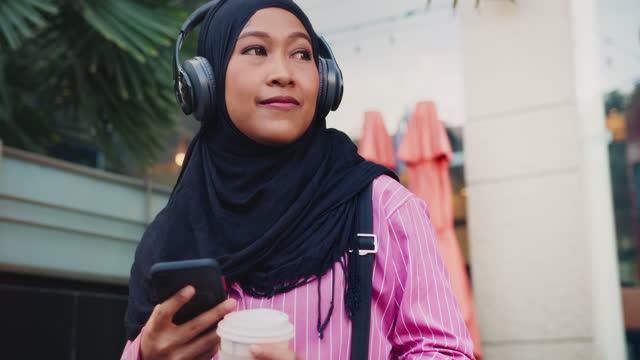 vídeos y material grabado en eventos de stock de primer plano: mujer musulmana del sudeste asiático que usa hiyab y auriculares inalámbricos escuchar podcast o música en el teléfono móvil mientras sostiene una taza de café y camina para trabajar en la ciudad por la mañana. - east asian ethnicity