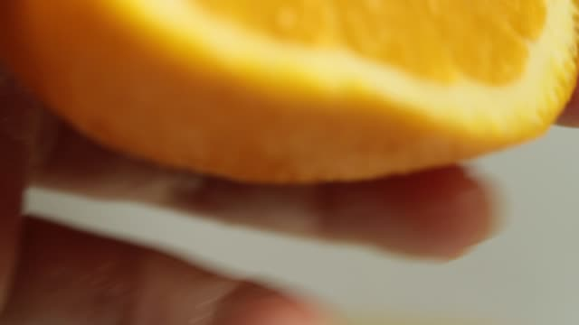 close-up squeezing orange slice - orange stock videos & royalty-free footage