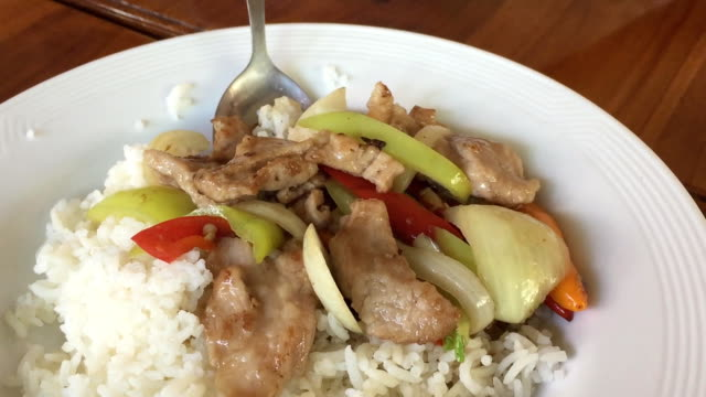 close-up stir-fried pork with green and red bell pepper over rice - red bell pepper stock videos & royalty-free footage