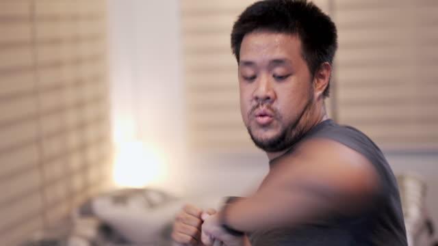 vídeos y material grabado en eventos de stock de sub-up sudor hombre asiático haciendo ejercicio de golpes de codo en casa en el dormitorio - codo