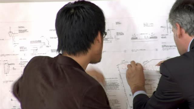 vídeos de stock, filmes e b-roll de close-up three businesspeople talking and using drawing board - prancheta