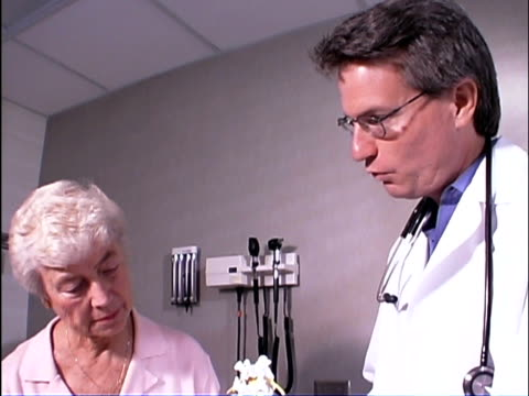 close-up tilt down of patient and doctor talking about osteoporosis as he shows her a spine during a medical exam. - osteoporosis stock videos & royalty-free footage