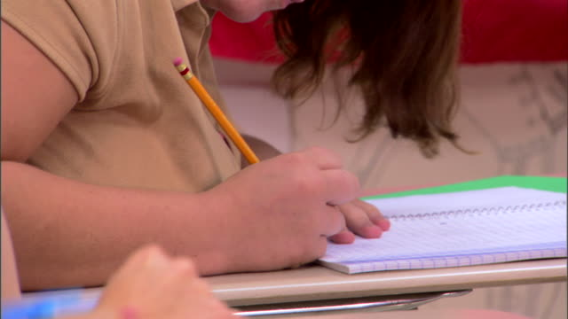 Close-up tilt down of student's hands taking notes during class.