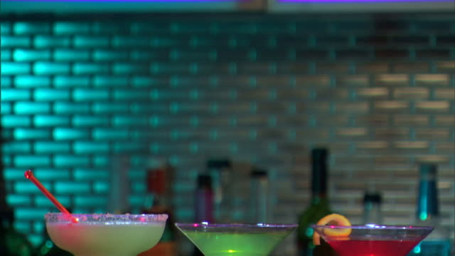 close-up tilt down to martinis and a margarita on a bar. - margaritas stock videos and b-roll footage