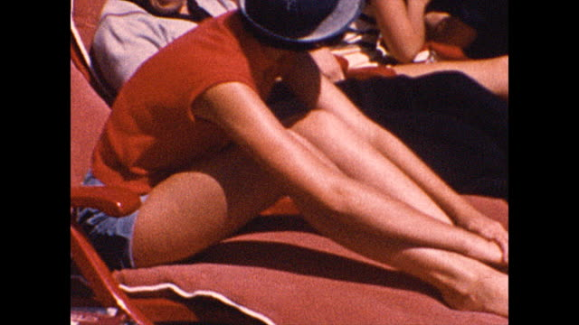 close-up tilt up of a woman's legs. close-up of a woman at the edge of a boat. mid shot of men and women sunbathing on the deck of a boat in 1952.... - passenger ship stock videos & royalty-free footage