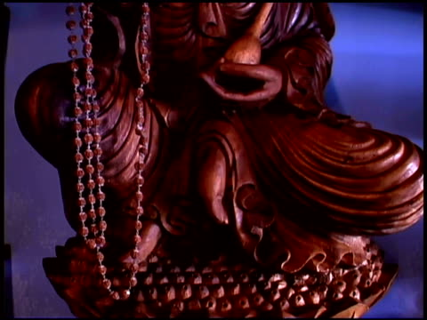 close-up tilt up of an ornate buddhist statue carved out of wood. - female likeness stock videos & royalty-free footage