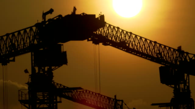Closeup time lapse of sunset of a construction site in silhouette in Singapore