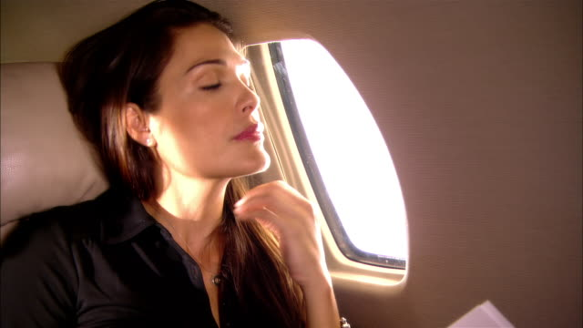 Close-up Tired businesswoman rubbling her neck while flying in private jet/ Miami, Florida, USA