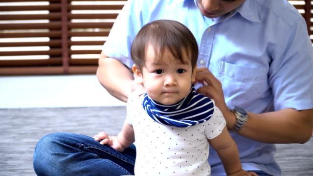 close-up to 2 year old son getting dressed from his young father - modern manhood stock videos & royalty-free footage