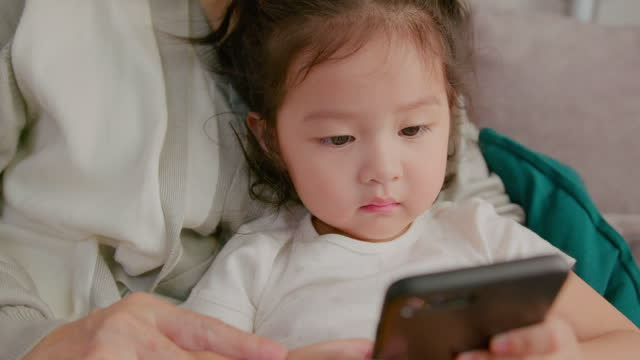 close-up toddler girl using mobile phone with grandmother at home. - digital native stock videos & royalty-free footage