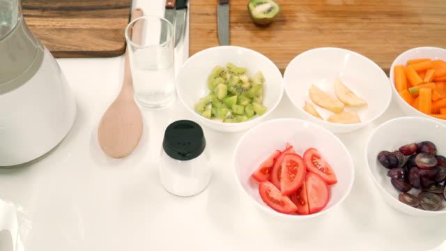 vidéos et rushes de vue de dessus de close-up: fruits et légumes dans un bol pour faire une boisson glacée en bonne santé - aliment en portion