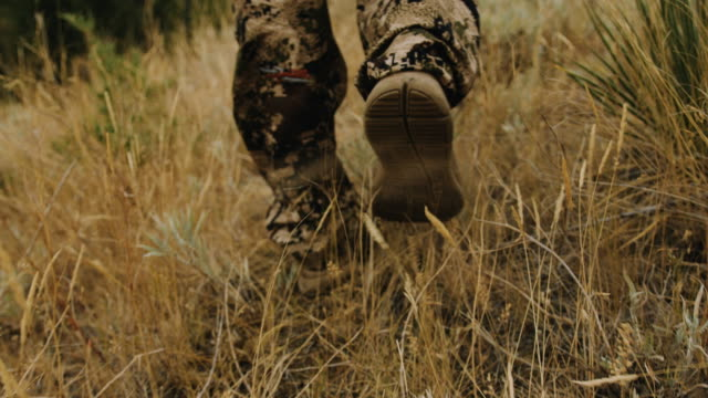 Closeup tracking shot of a hunter's feet as he walks through the wild grass.