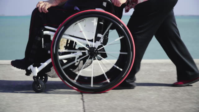 close-up tracking shot of a senior woman taking her husband, who is in a wheelchair, for a walk in a park - 車いす点の映像素材/bロール
