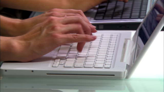 close-up two customer service representatives using laptops side by side - side by side stock videos & royalty-free footage