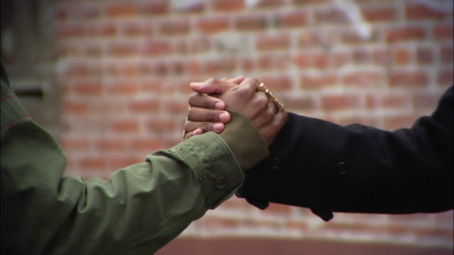 stockvideo's en b-roll-footage met close-up two men giving each other street handshakes / new york city, new york, usa - iemand een hand geven