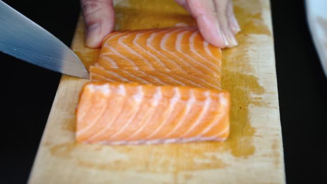 vídeos de stock e filmes b-roll de 4k close-up using knife cut and slice fresh salmon on wooden chopping board - filete de salmão