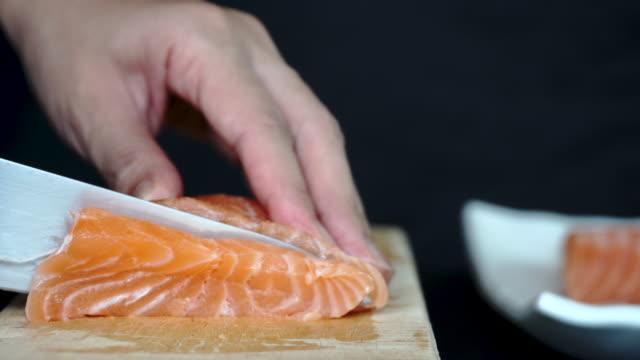vídeos de stock e filmes b-roll de 4k close-up using knife slice fresh salmon on wooden chopping board - filete de salmão