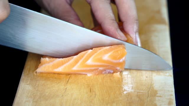 vídeos de stock e filmes b-roll de 4k close-up using knife slice fresh salmon on wooden chopping board - sashimi