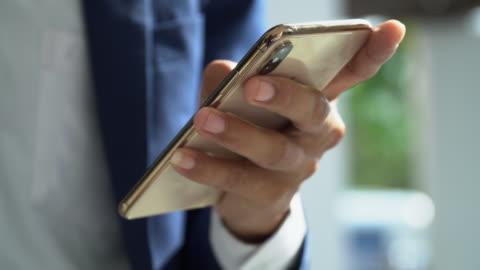 närbild video av affärsmannens händer surfa på internet med smart telefon - app bildbanksvideor och videomaterial från bakom kulisserna
