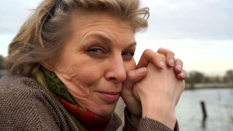 närbild video porträtt av den vackra 50 år gammal kvinnan med en blandade känslor i ansiktet. - 50 54 år bildbanksvideor och videomaterial från bakom kulisserna