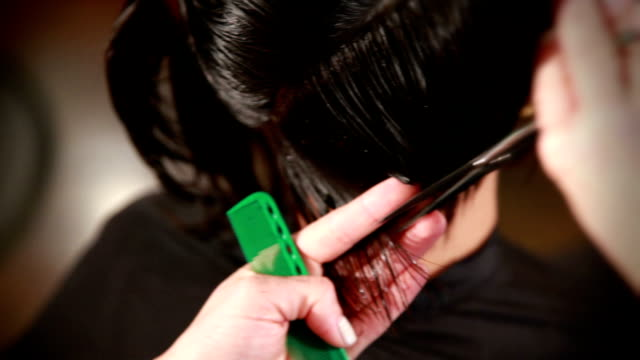 closeup view from above as stylist cuts a young woman's hair - scissors stock videos and b-roll footage