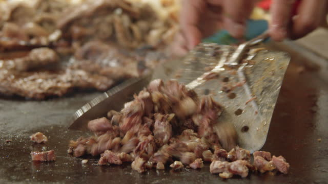 close-up view of a chef chopping griddle-fried beef for tacos at a local taco restaurant - taco stand stock videos & royalty-free footage