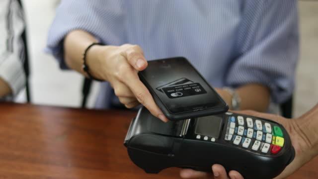 vídeos y material grabado en eventos de stock de vista de primer plano de una transacción de nfc con un smartphone - pago por móvil