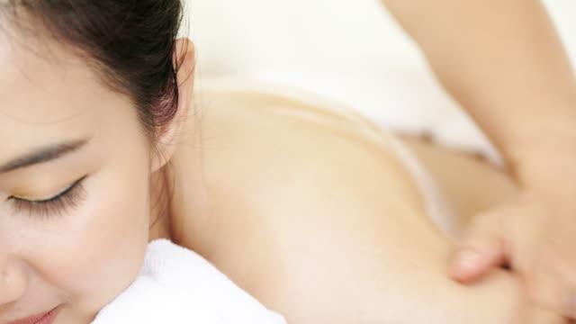 彼女のタイ式マッサージを持つ油を塗った肌を持つ若い女性のクローズ アップ ビューを前後スパクラブで肩に。 - マッサージ台点の映像素材/bロール