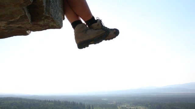 close-up view of climber's feet dangling from summit at sunrise - at the edge of stock videos & royalty-free footage