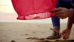 Closeup view of hands lightening before launching red paper lantern. Female hands holding lantern with fire before to let it fly standing by the beach