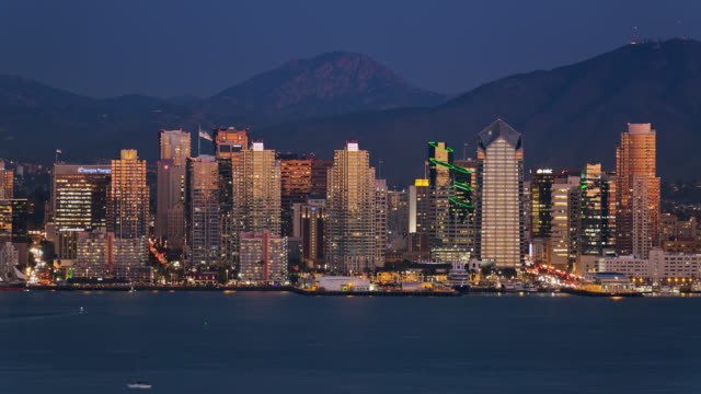 T/L Close-up view of San Diego skyline at night with mountains in the background / San Diego, California, USA