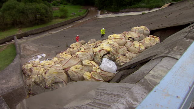 close-up view of sandbags on the damaged toddbrook reservoir whilst concrete is poured in an attempt to reinforce the structure - dam stock videos & royalty-free footage